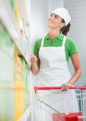 Supermarket worker with cart — Stock Photo