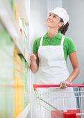 Supermarket worker with cart — Zdjęcie stockowe