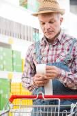 Farmer checking bills at supermarket — Stock Photo