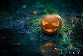Creepy pumpkin next to a water stream — Stock Photo