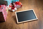 Beautifully wrapped gifts with blackboard — Stock Photo