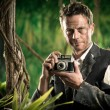 Photoreporter walking in the jungle with vintage camera — Stock Photo #54005895