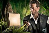 Businessman lost in jungle — Stock Photo