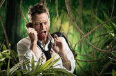 Furious businessman on the phone lost in jungle — Foto Stock