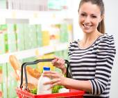 Smiling woman with shopping basket — Stock Photo