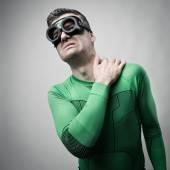 Superhero with stiff neck — Stock Photo
