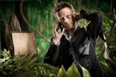 Lost businessman with mobile phone — Stock Photo