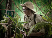 Explorer in jungle finding an exit sign — Стоковое фото