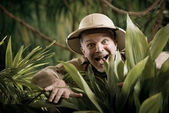 Adventurer peeking through plants — Stock Photo