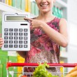Woman pointing to calculator at supermarket — Stock Photo #54962067