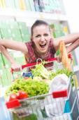 Angry woman pushing shopping cart — Stock Photo