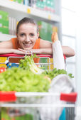 Woman leaning on shopping cart — Stock Photo