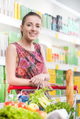 Woman at supermarket with shopping cart — Foto Stock