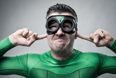 Superhero plugging ears with fingers — Stock Photo