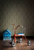 Vintage tricycle with doll house — Stock Photo
