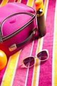 Towel with bag, sunglasses and sun creams — Stock Photo