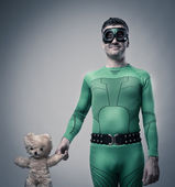 Superhero holding a teddy bear — Stock Photo