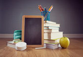 Chalkboard, apple and colorful stationery. — Stock Photo