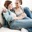 Girls smiling and flirting on sofa — Stock Photo #56611129