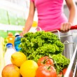 Woman pushing a shopping cart — Stock Photo #56615039