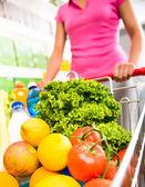 Woman pushing a shopping cart — Stock Photo