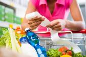 Woman checking grocery receipt — Stock Photo