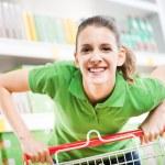 Woman pushing shopping cart — Stock Photo #56620565