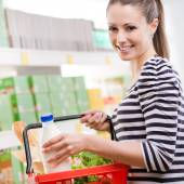 Smiling woman with shopping basket — Stockfoto