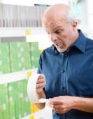 Senior man checking  grocery receipt. — Stockfoto