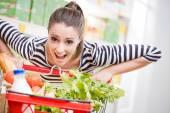 Woman pushing a full shopping cart — Foto de Stock