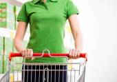 Woman with trolley at supermarket — Stock Photo
