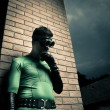 Cool superhero leaning to a brick wall — Stock Photo #58022541