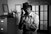 Film noir: detective holding a revolver and posing — Foto de Stock