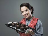 Vintage housewife with muffins — Stock Photo