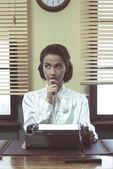 Pensive secretary with typewriter — Stock Photo