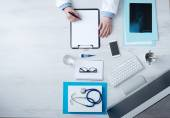 Doctor writing medical records — Stock Photo