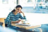 Woman at the cafe with headphones — Stock Photo