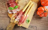 Grissini bread sticks with ham — Stockfoto