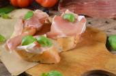 Bruschetta with prosciutto and basil leaves — ストック写真