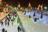 People skating near decorations and illuminations at winter nigh — Stock Photo