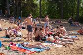 Girls and guys sunbathing in beach — Stock Photo