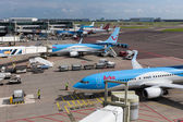 Schiphol airport with workers and departing and arriving airplanes — Stock Photo