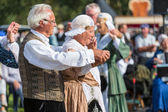 Eldery man and woman demonstrating an old Dutch folk dance during a Dutch festival — Stock Photo