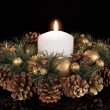 Christmas decoration with a white candle and pine apples at a black background — Stok fotoğraf #58813413