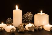Burning candles with pine apples and gilded stars on a black background — Foto de Stock