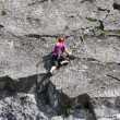 Woman climbing a vertical rock along river Meuse in Belgium — Stock Photo #72396185