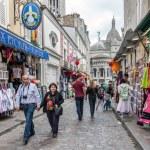 Постер, плакат: Tourists walking near the gift shops of Montmartre Paris France