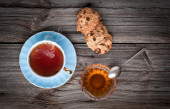Cup of tea, cookies stack and honey on a wooden background — Stock Photo