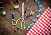 Vintage Background with sewing tools and colored tape. Sewing kit. Scissors, bobbins with thread and needles on the old wooden background — Stock Photo