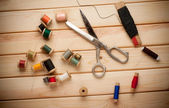 Sewing kit. Scissors, bobbins with thread and needles on the old wooden background — Stock Photo